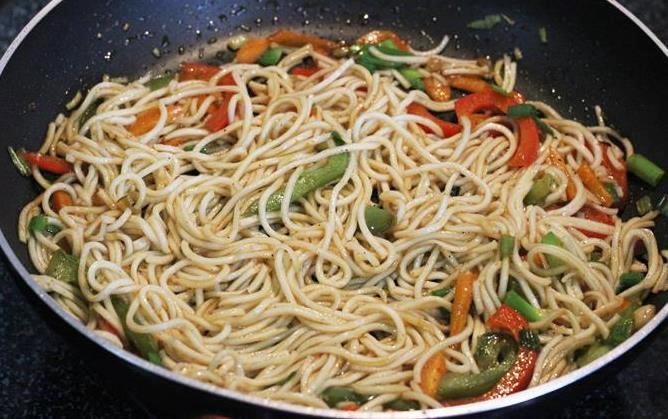 tossing veg hakka noodles in veggies sauces