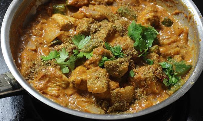 sprinkling garam masala coriander leaves for chicken karahi recipe