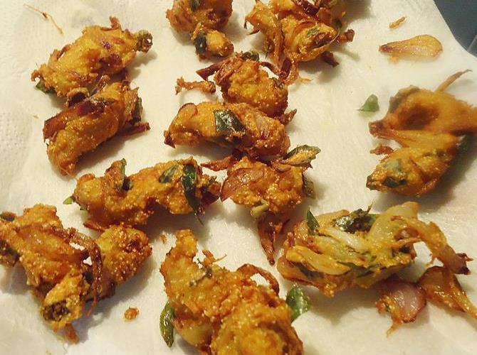 draining golden fried pakora on tissues to make chicken pakoda recipe