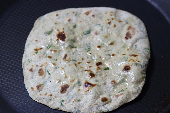 smearing ghee on one side to make methi paratha recipe