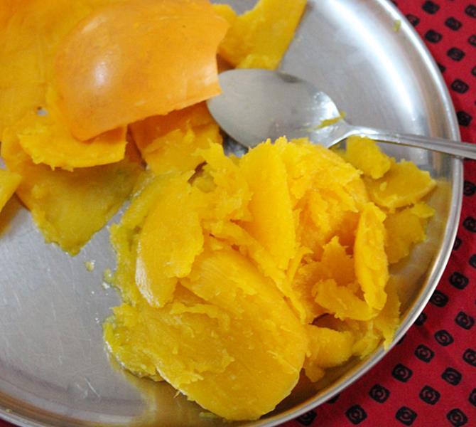 scooping the pulp to make pumpkin kheer recipe