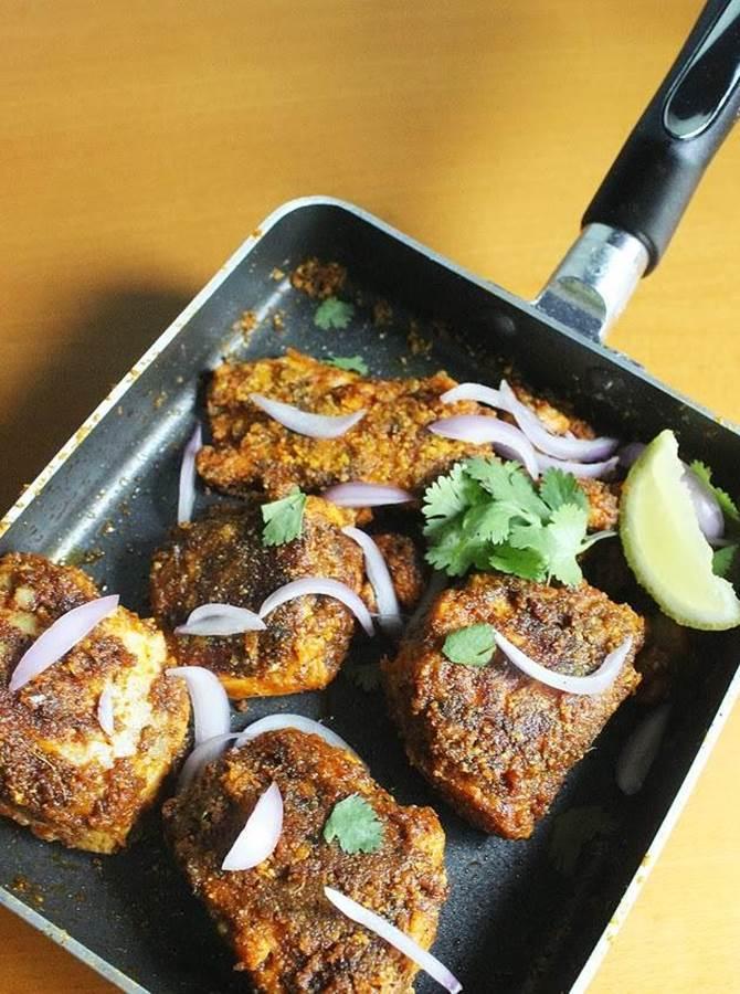 flipping roasting fillets on pan to make amritsari tawa fish fry