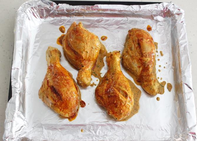 red chili oil basting while grilling tandoori chicken in oven