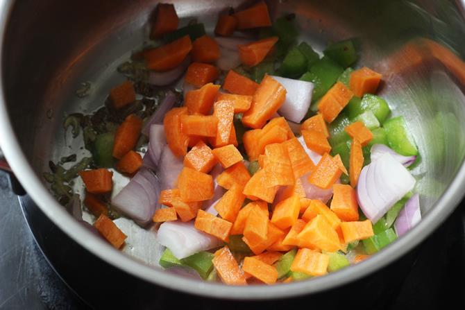 sauteing carrots potato gobi capsicum for making oats khichdi recipe